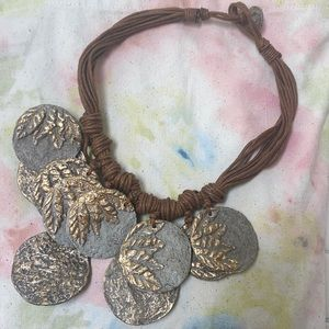 Decorative paper mache disk necklace.